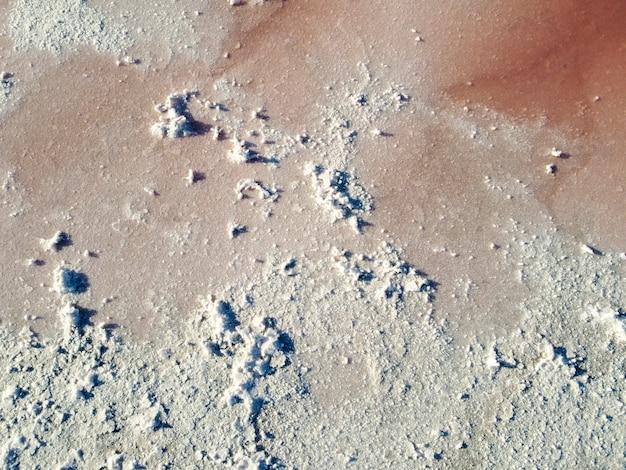 Sale bianco su un lago rosa formatosi a seguito dell'evaporazione. sfondo di astrazione.