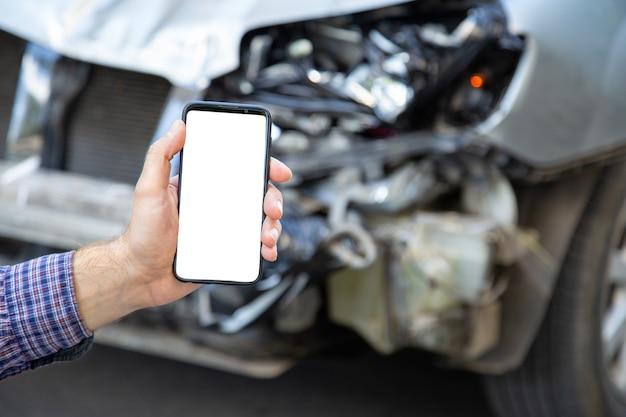Telefono cellulare con schermo bianco in mani maschili dopo un incidente d'auto. servizio di assicurazione, scuola guida, chiamata di carro attrezzi o app web sopra incidente d'auto. smartphone davanti all'auto distrutta.