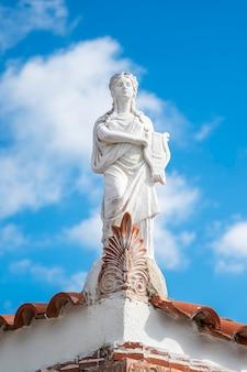 Scultura bianca in pietra in stile greco antico, una donna situata sul bordo di un tetto di un edificio in grecia