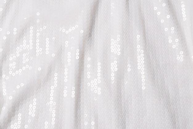 Sfondo di paillettes bianco. tessuto di paillettes bianco lucido. vista dall'alto.