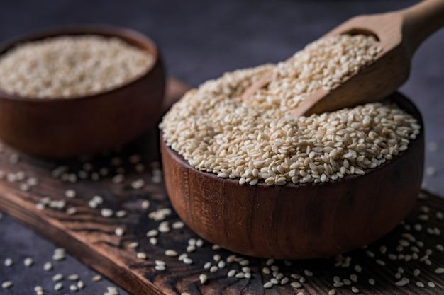 Sesamo bianco in un cucchiaio di legno sul tavolo scuro, olio di sesamo in barattolo e semi.