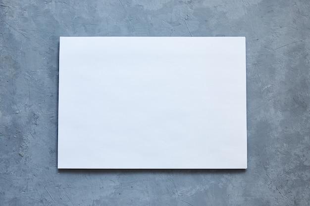 Foglio bianco su sfondo grigio cemento.