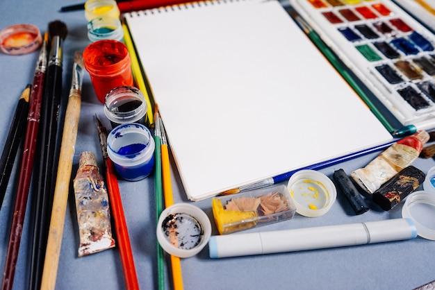Foglio di carta bianco su uno sfondo di vernici multicolori