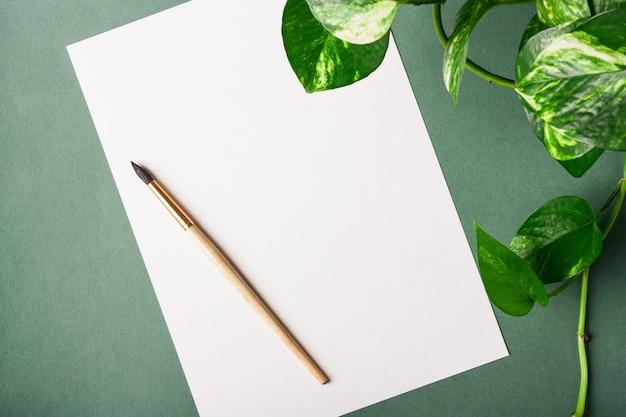Foglio di carta bianco, pennello e pianta su sfondo verde