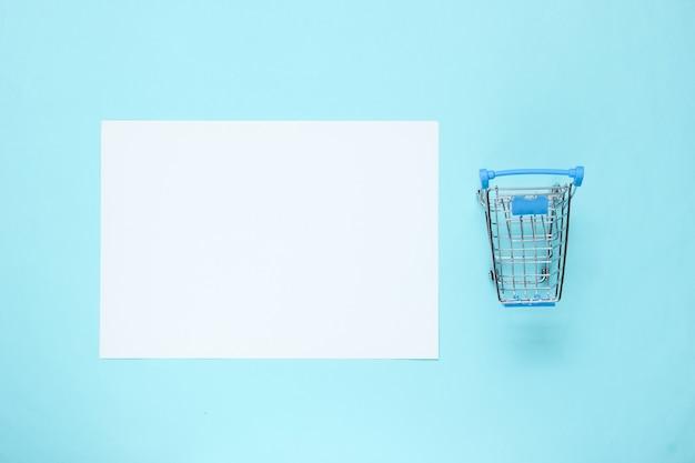 Foglio di carta bianco per lo spazio della copia, mini carrello sulla tavola blu. tavolo da shopping creativo
