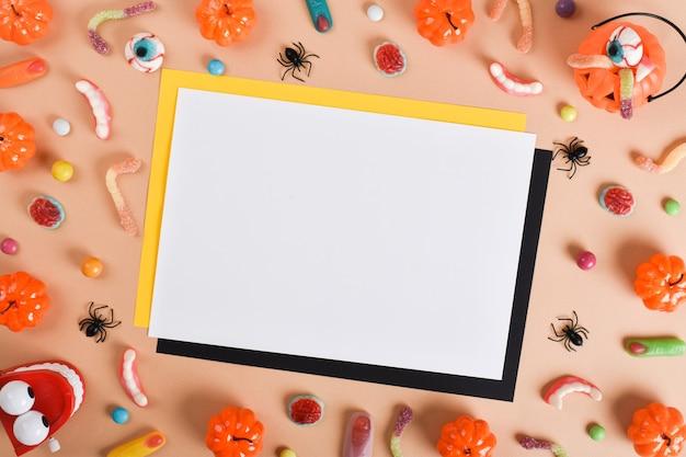 Un foglio di carta bianco accanto a vari dolci su uno sfondo arancione con un posto per il testo. felice halloween.
