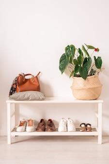 Mensole bianche con calzature sportive e casual, borsa in pelle marrone e cesto di piante domestiche dalla parete della stanza domestica o dello studio