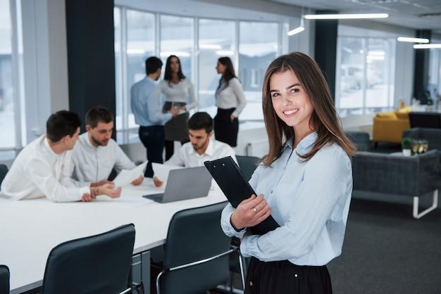 In camicia bianca e pantaloni neri. il ritratto della ragazza sta nell'ufficio con gli impiegati a fondo