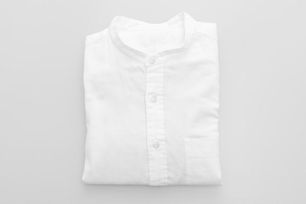 Piega della camicia bianca su una superficie bianca