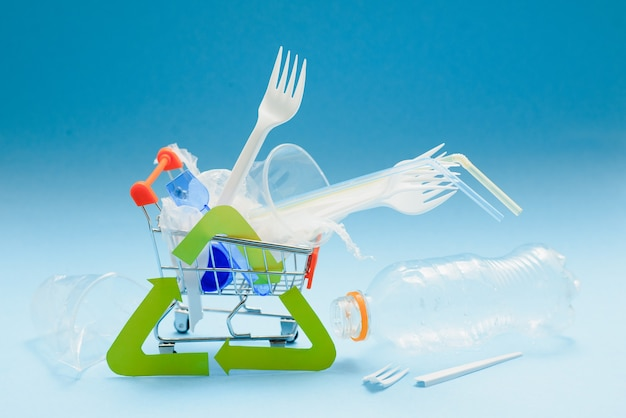 Plastica monouso bianca e altri oggetti in plastica su sfondo blu