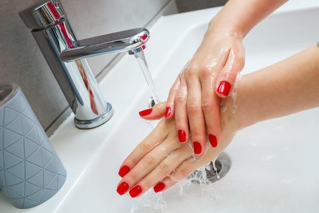 Lavandino bianco con rubinetto d'argento in bagno. lattina grigia con sapone liquido per le mani. apertura dell'acqua del rubinetto, igiene personale delle mani. lavarsi le mani sotto l'acqua corrente