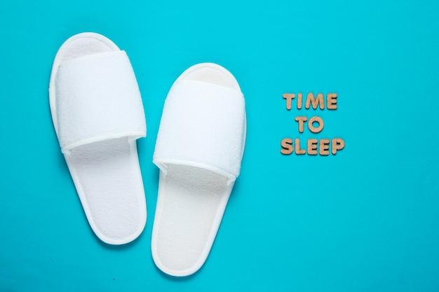 Pantofole bianche dell'hotel di sonno isolate sull'azzurro