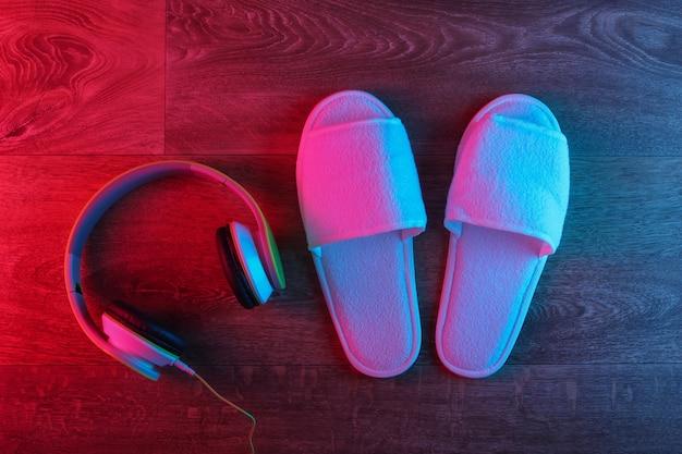 Pantofole bianche con cuffie sul pavimento di legno con bagliore sfumato rosso-blu al neon
