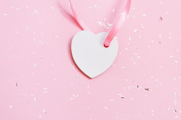 Piccolo cuore bianco su superficie rosa con paillettes