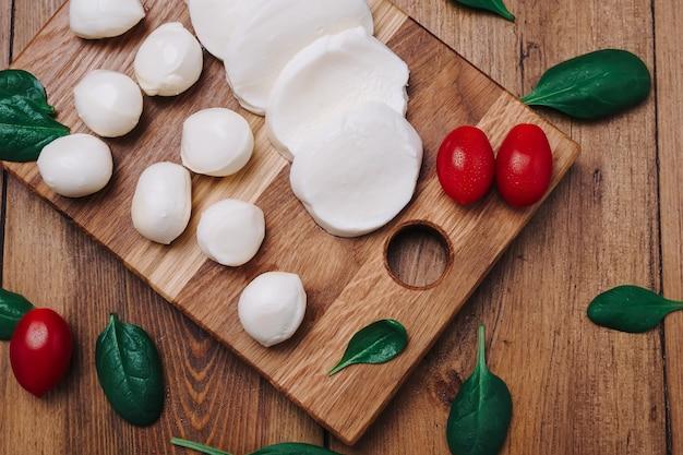 Mozzarella bianca piccola, palline di formaggio, foglie di spinaci e pomodori su tavola di legno