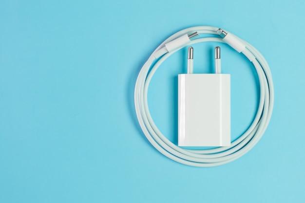 Un cavo del caricatore del telefono astuto bianco con il usb ad alta velocità del fulmine un connettore e un adattatore isolati sui precedenti blu