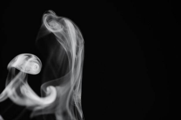 Fumo bianco su sfondo nero. trama di fumo. mazze di fumo bianco su sfondo scuro per la sovrapposizione