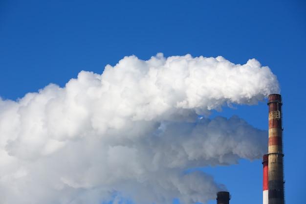 Il fumo bianco proviene da tubi contro il cielo blu Foto Premium