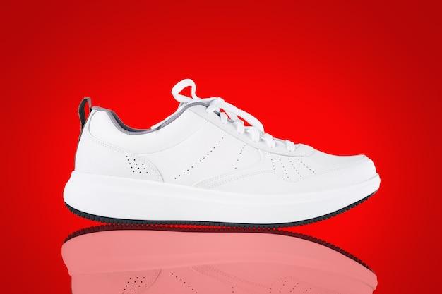 Sneaker bianca isolata su sfondo rosso nuova scarpa sportiva senza marchio