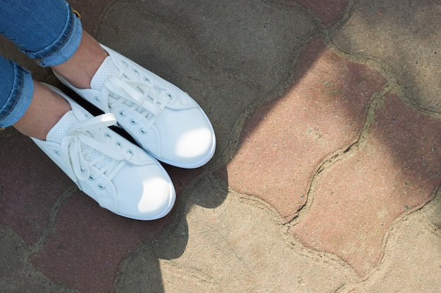 Scarpe da ginnastica bianche sui piedini femminili in blue jeans sui precedenti dell'asfalto.