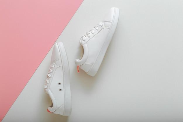Sneakers bianche, scarpe da donna in pelle bianca con lacci su sfondo rosa. paio di scarpe da ginnastica alla moda comode scarpe da donna hipster di abbigliamento sportivo. vista dall'alto con copia spazio.
