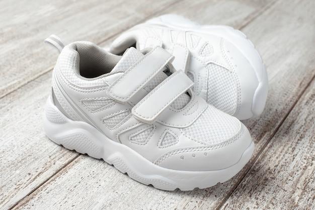Sneakers bianche su sfondo chiaro un paio di sneakers sportive per bambini in pelle cucite con un tessuto ...