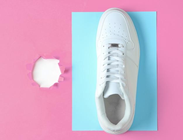Scarpe da ginnastica bianche su carta rosa con foro strappato per copia spazio