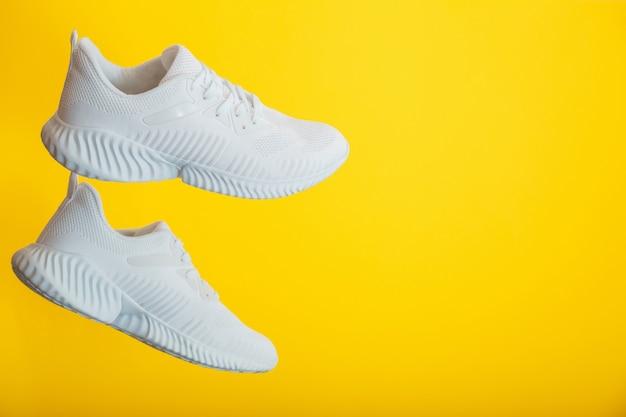 Le scarpe da ginnastica bianche volano su sfondo giallo di colore. coppia di scarpe da ginnastica bianche da uomo sportive da jogging.