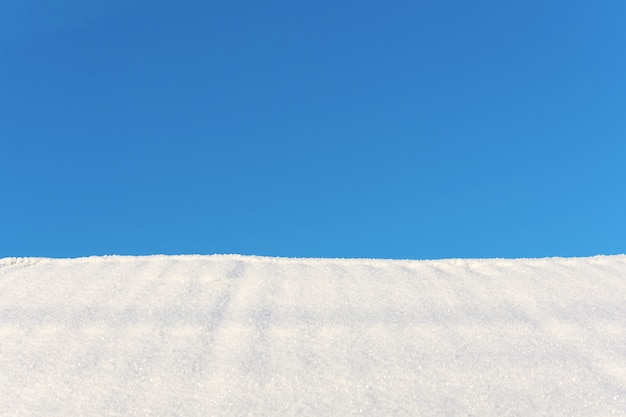 Il bianco della neve e il cielo blu come sfondo invernale, copia spazio disponibile.