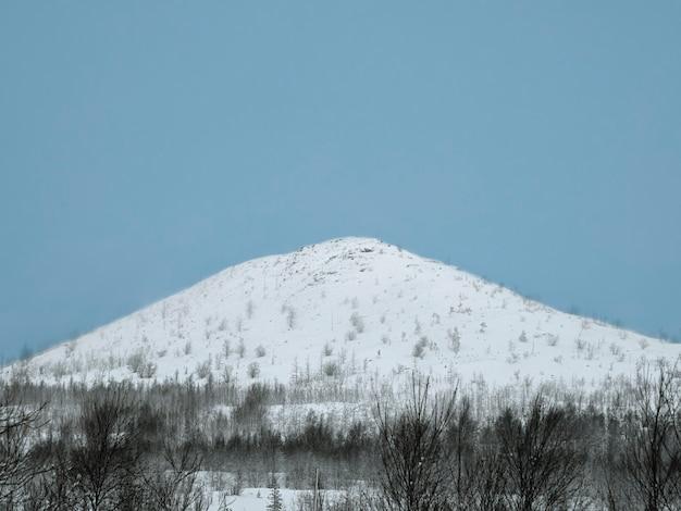 La neve bianca copriva la cima della collina. snowy arctic hill.