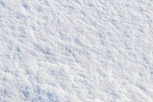 Struttura bianca della neve in tempo soleggiato. sfondo invernale