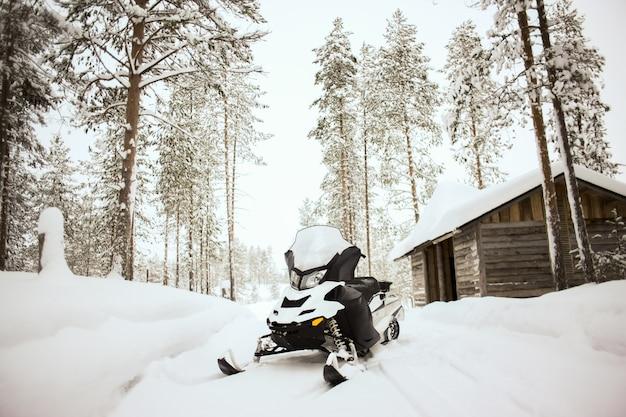 La motoslitta bianca è in piedi su una neve all'aperto