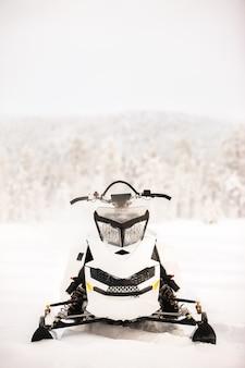 La motoslitta bianca è in piedi su un campo innevato sullo sfondo di un paesaggio panoramico invernale. cornice verticale