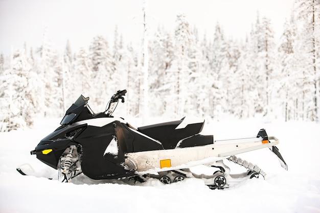 La motoslitta bianca è in piedi su un campo innevato sullo sfondo di un paesaggio panoramico invernale