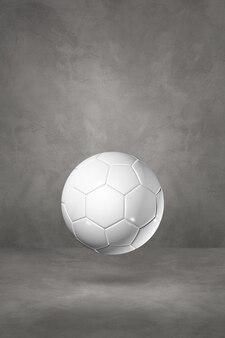 Pallone da calcio bianco isolato su uno studio concreto