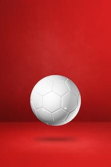 Pallone da calcio bianco isolato su uno sfondo rosso per studio. illustrazione 3d