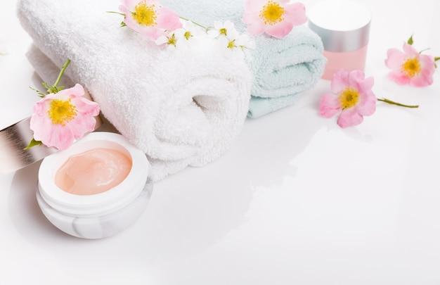 Asciugamano spa bianco con rose selvatiche e crema su sfondo bianco, concetto di spa organica estiva