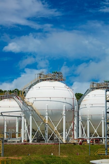 Serbatoi di propano sferici bianchi che contengono il cielo blu del fondo del gas combustibile.