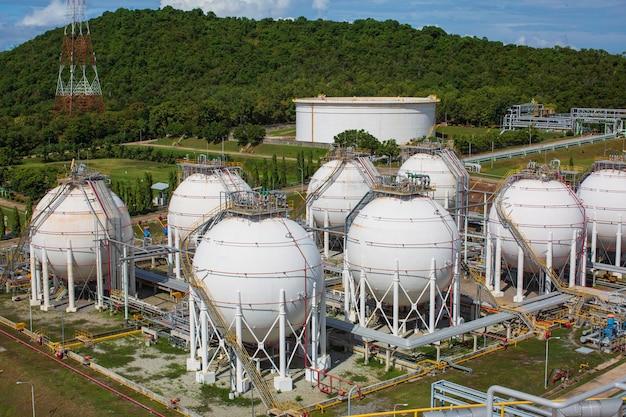Serbatoi di propano sferici bianchi contenenti gas combustibile in montagna.