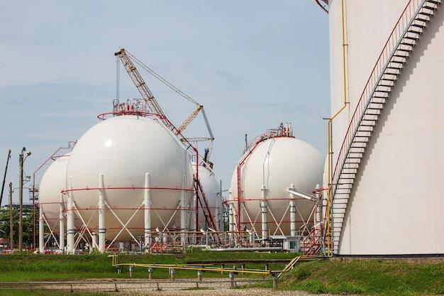 Serbatoi di propano sferici bianchi contenenti gasdotto e lavori di impalcatura