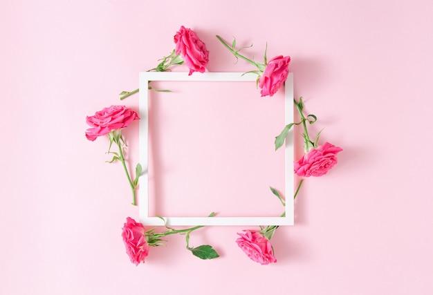 Cornice quadrata bianca con rose rosa su sfondo rosa. composizione di arte floreale minimalista. copia spazio