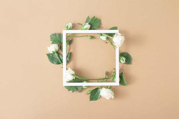 Cornice quadrata bianca con rose bianche su sfondo marrone chiaro beige. composizione di arte floreale minimalista