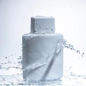 Bottiglia di vetro quadrata bianca su sfondo bianco e spruzzi d'acqua