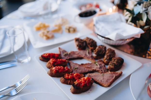 Piatto quadrato bianco con fette di bruschetta e piatto di formaggio sul tavolo apparecchiato per le vacanze