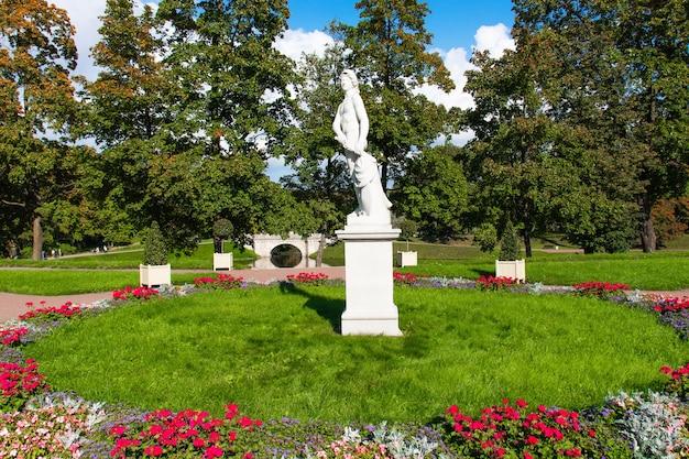 Statua bianca dell'uomo con la spada nel mezzo del letto di fiori sullo sfondo di alberi verdi nel parco - russia, gatchina, settembre 2021