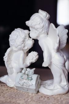 Statuetta bianca di due angeli sul tavolo. avvicinamento. bacio.