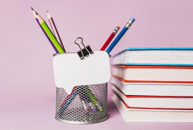 Adesivo bianco, libri, blocco note e pensil sul posto di lavoro. mock up in copia spazio ufficio sfondo viola. è importante non dimenticare la nota