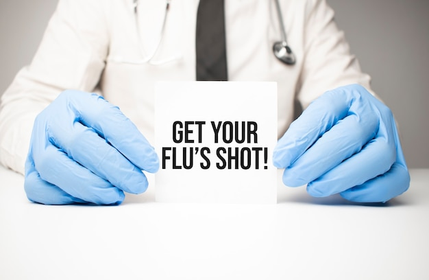 Adesivo bianco con testo ottieni il vaccino antinfluenzale nelle mani del medico con uno stetoscopio