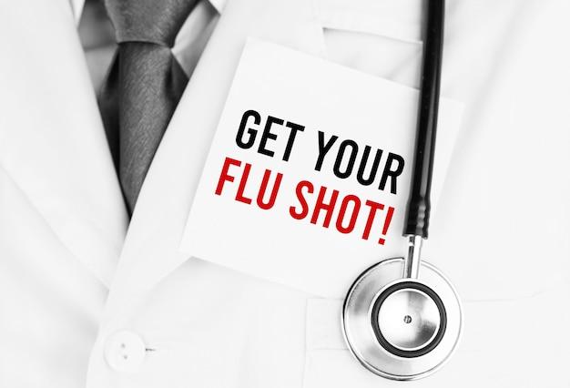 Adesivo bianco con testo ottieni il tuo vaccino antinfluenzale sdraiato sulla veste medica con uno stetoscopio