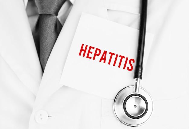 Adesivo bianco con testo epatite sdraiato sulla veste medica con uno stetoscopio